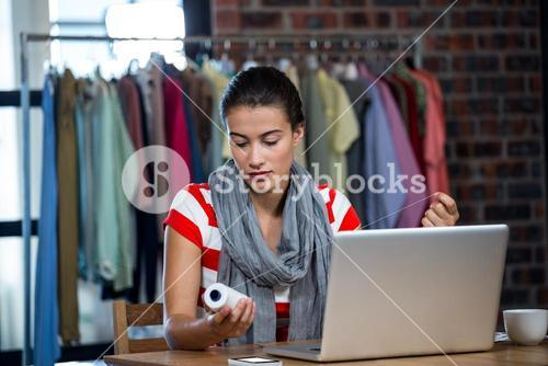 Woman with a laptop holding a thread reel