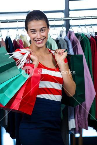 Happy woman holding shopping bags in clothes shop
