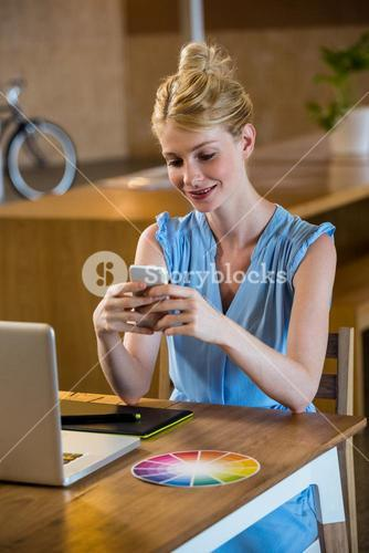 Graphic designer text messaging on mobile while using laptop