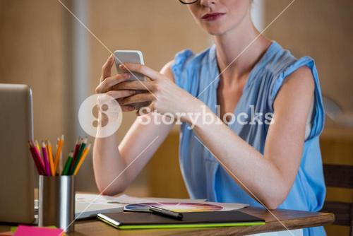 Graphic designer in office sitting at desk and text messaging on mobile phone