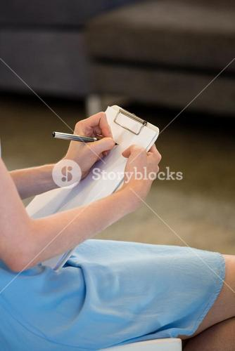 Woman writing note on clipboard