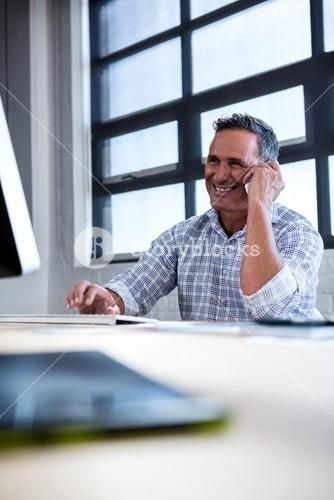 Man talking on mobile phone while using computer