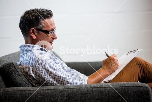 Man writing note on clipboard