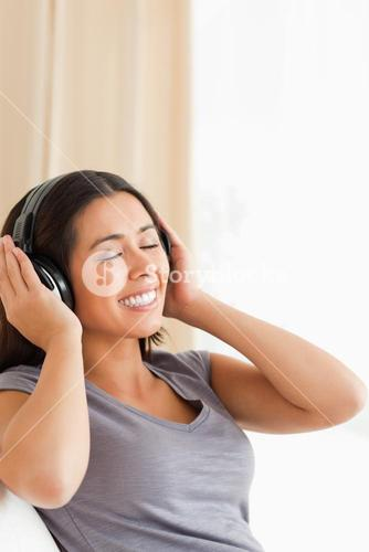 smiling woman sitting on sofa with earphones and eyes closed