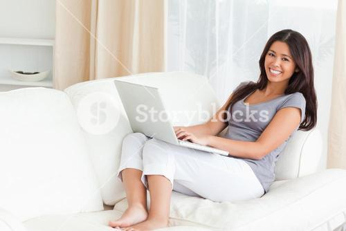 working lady with notebook on sofa smiling into camera