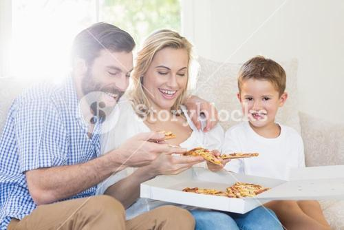 Parents and child sitting on sofa and having pizza