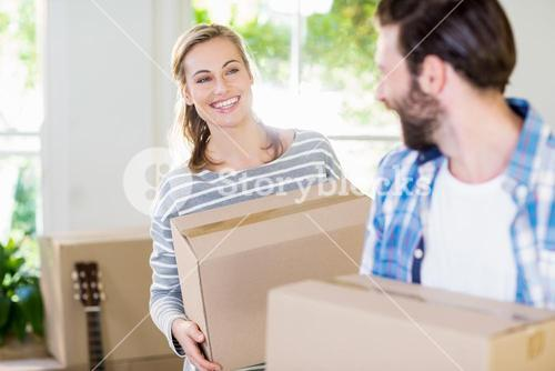 Happy young couple holding cardboard boxes
