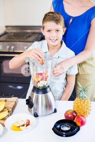 Mother assisting son to prepare juice