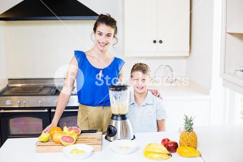 Mother and son standing at table in kitchen