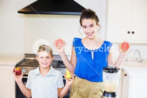 Mother and son holding fruits in kitchen