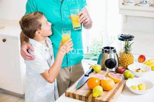 Father and son holding glass of a juice
