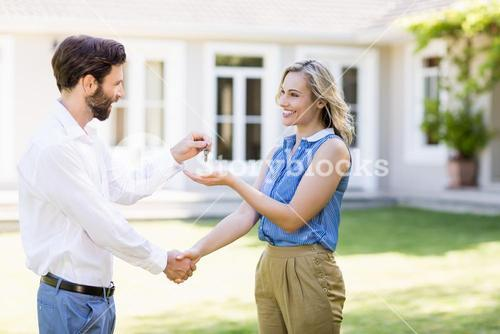 Real estate agent giving keys to woman