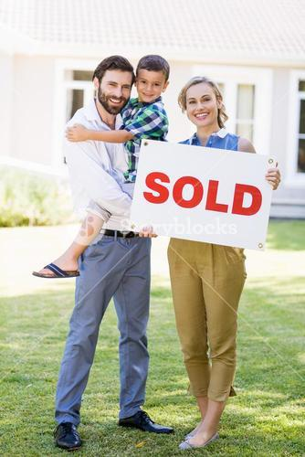 Family standing outside home with sold sign