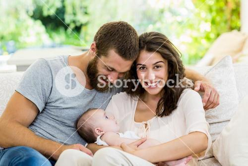 Happy parents with their baby in living room