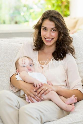 Mother holding her baby on lap in living room