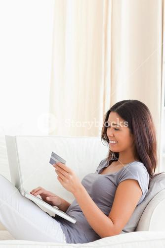 goodlooking woman sitting on sofa holding card