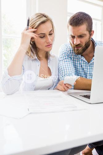 Worried couple looking at mobile phone