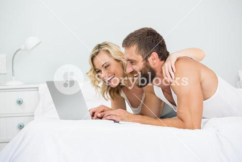 Couple using laptop on bed