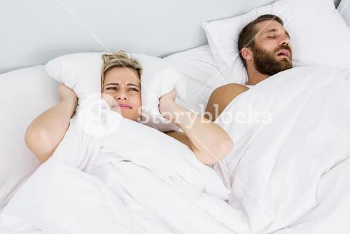 Woman covering ears while man snoring on bed