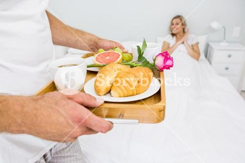 Man carrying breakfast for a woman in bed