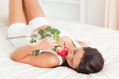 cute woman with rose lying on bed