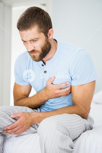 Young man having chest pain in bed
