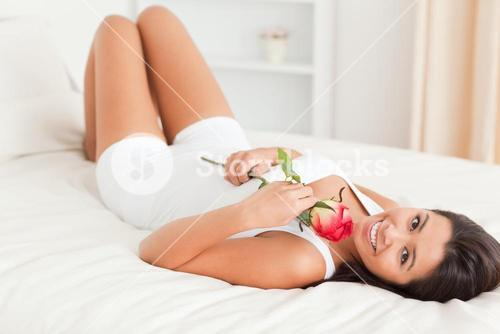 goodlooking woman with rose lying on bed looking into camera