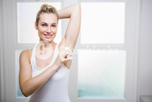 Young woman applying powder on her underarms