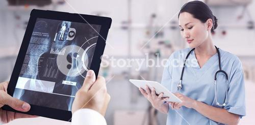Composite image of surgeon using digital tablet with group around table in hospital