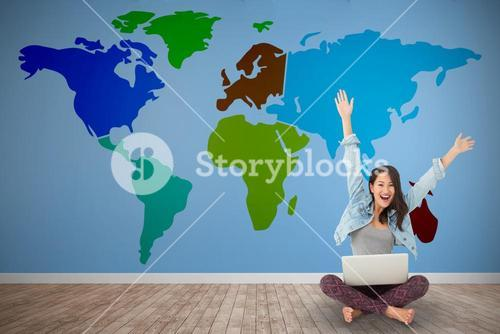 Composite image of asian woman cheering at camera with laptop sitting on floor