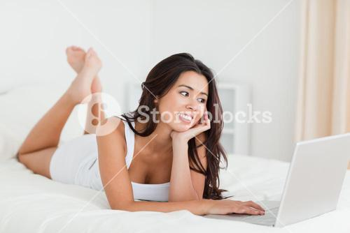 charming woman lying on bed with crossed legs and laptop