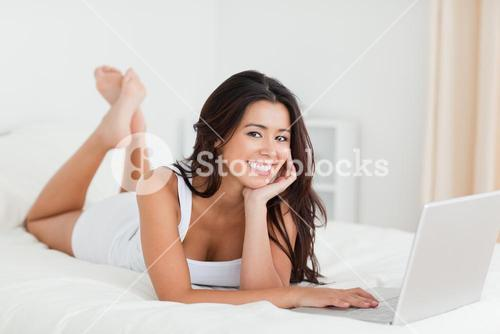 charming woman lying on bed with crossed legs and laptop looking into camera