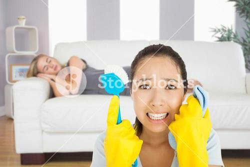 Composite image of distressed woman holding cloth and scrubbing brush