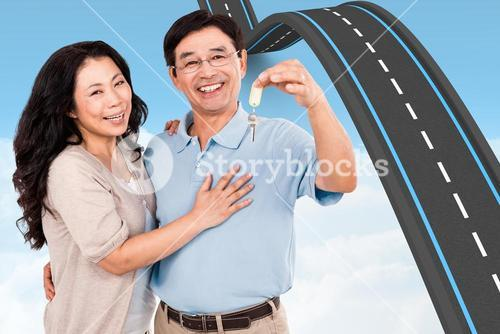 Composite image of smiling couple holding a set of keys