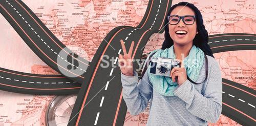 Composite image of asian woman holding digital camera and making peace sign with hand