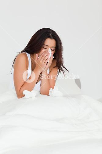 brunette woman having a cold sitting in bed