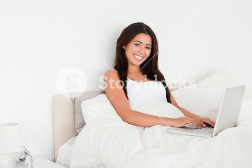 charming woman with notebook lying in bed looking into camera