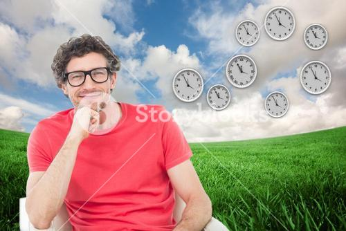 Composite image of happy businessman wearing reading glasses while sitting on chair