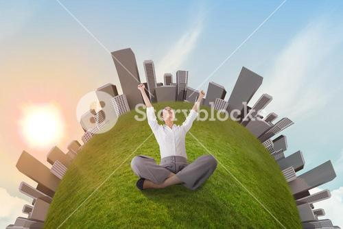 Cheering businesswoman sitting cross legged