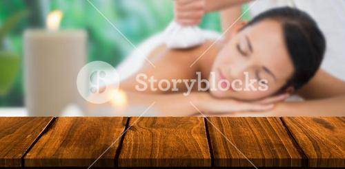 Composite image of beautiful brunette enjoying a herbal compress massage