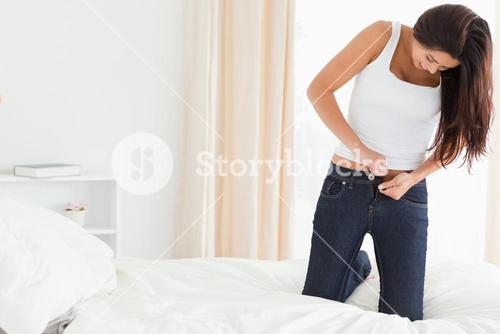 brunette woman kneeing on bed trying to close her jeans