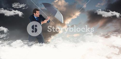 Composite image of man holding umbrella to protect himself from the rain