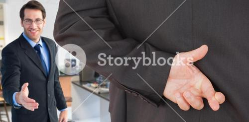 Composite image of businessman with fingers crossed