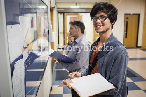 Portrait of smiling student standing in front of notice board