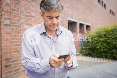Professor using mobile phone in campus