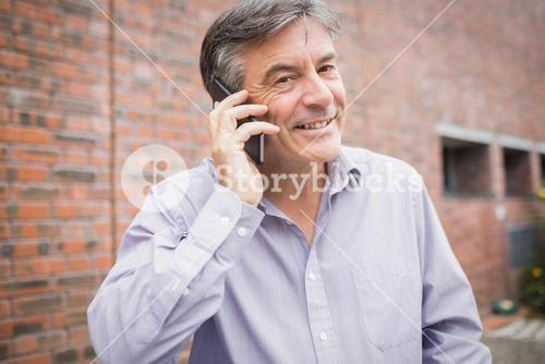 Portrait of happy professor talking on phone