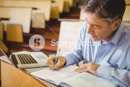 Professor writing in book at desk