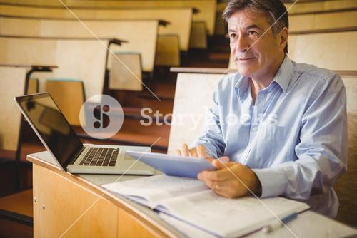 Thoughtful professor using digital tablet