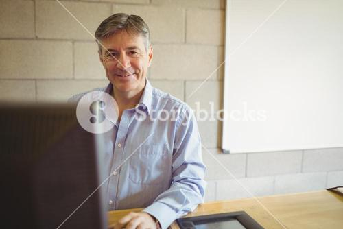 Portrait of professor sitting on desk