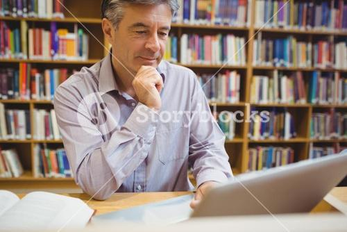 Professor sitting at desk using laptop
